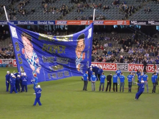 North Melbourne cheer squad with banner for Boomer's 350th game & Wells's 200th.