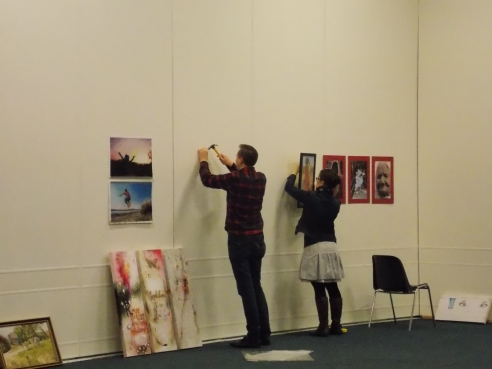 Ian left the office to come help us set up. Here he is helping Jess hang a few canvases.